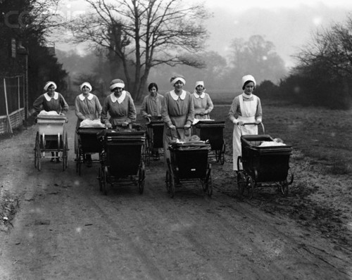 Trainee nannies at a Nursery Training Centre push prams